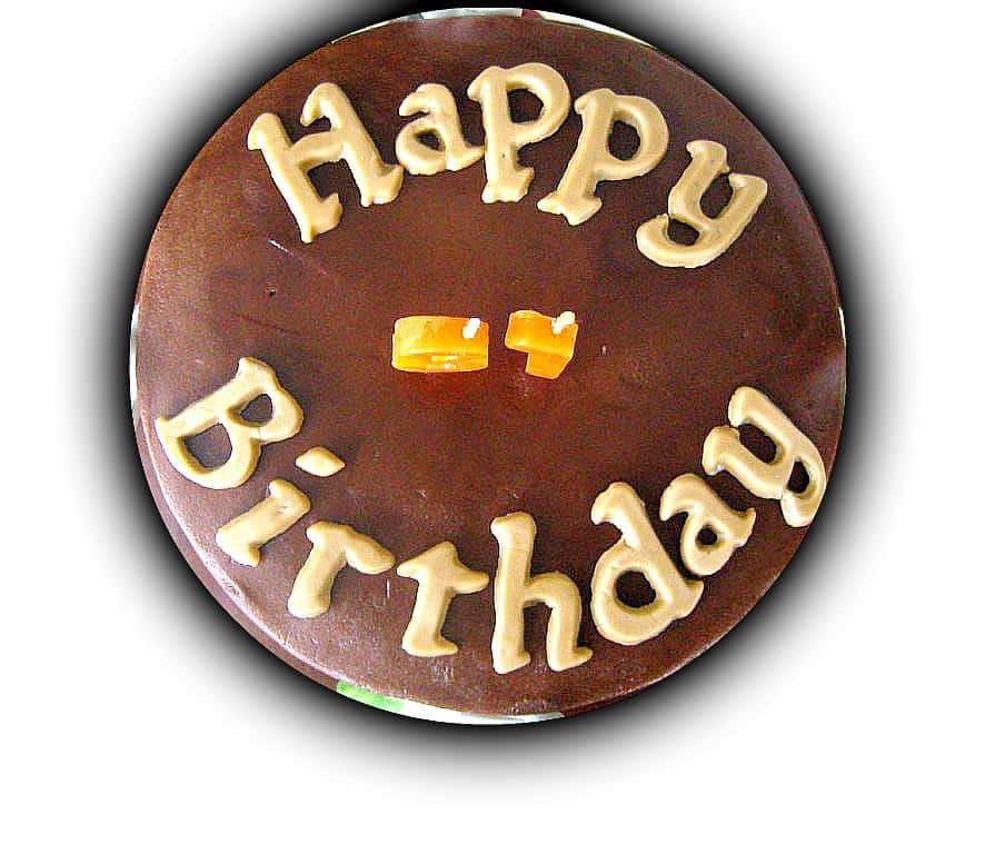 Top view of a chocolate cake with Happy Birthday alphabets and number candles