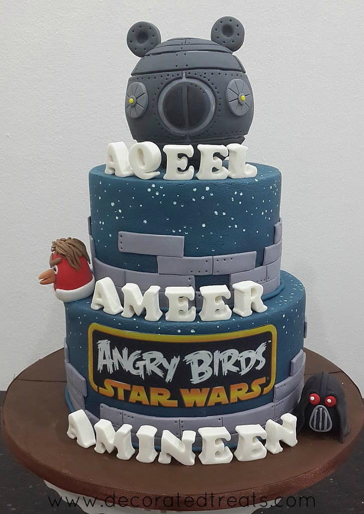 A 3 tier cake with Angry Birds Star War theme. Cake is decorated in grey, with Angry Birds characters in 3D.
