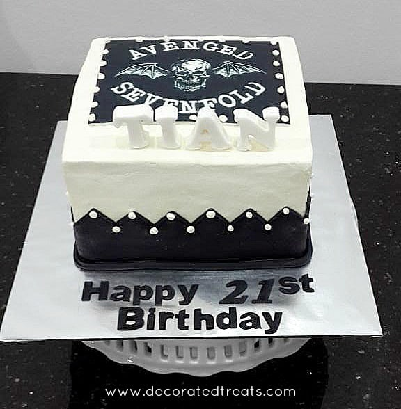 A square white cake decorated with Avenged Sevenfold image in black.