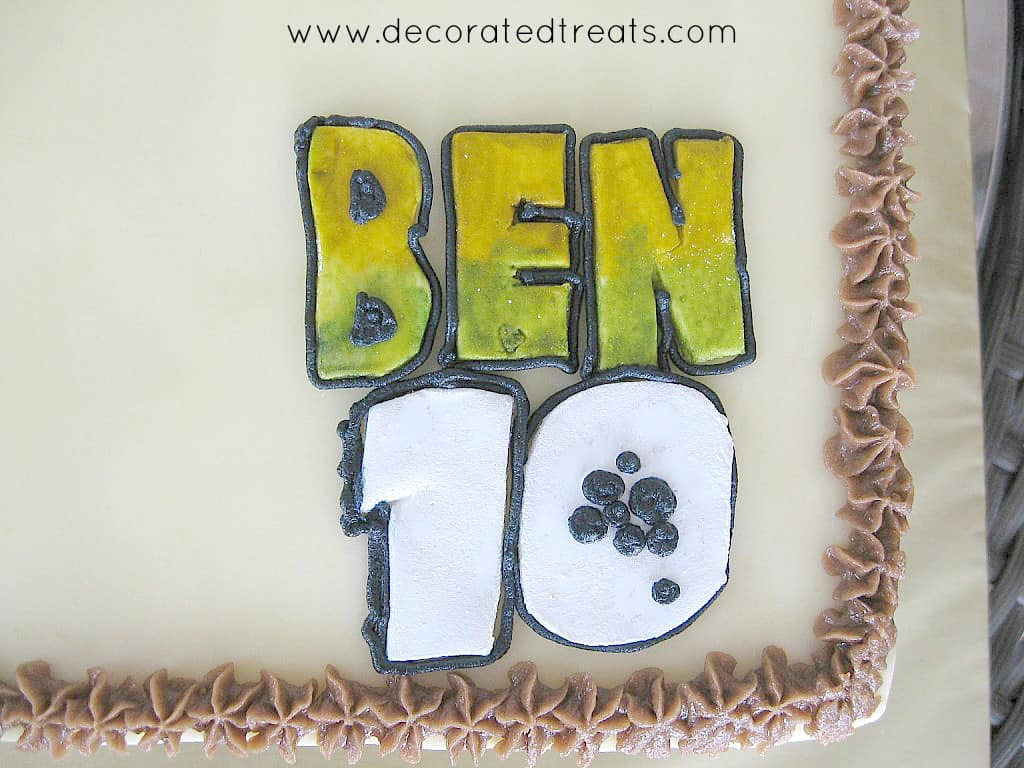 Ben 10 logo made of fondant in green and white, on a cake