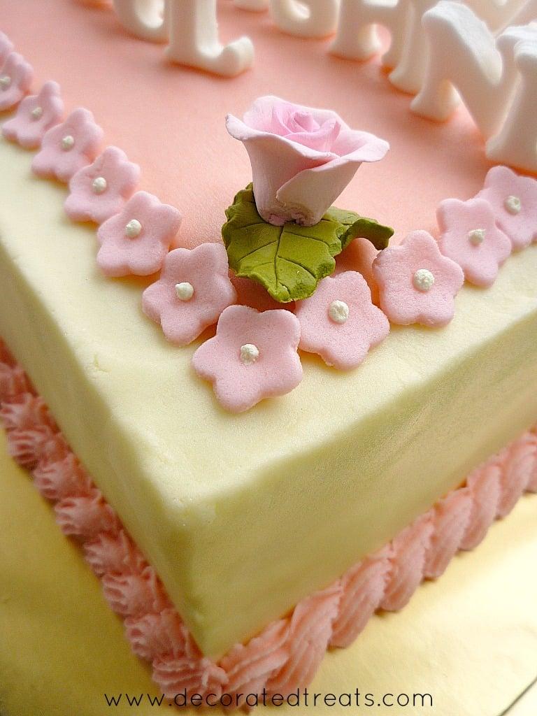 A pink gum paste rose bud on cake