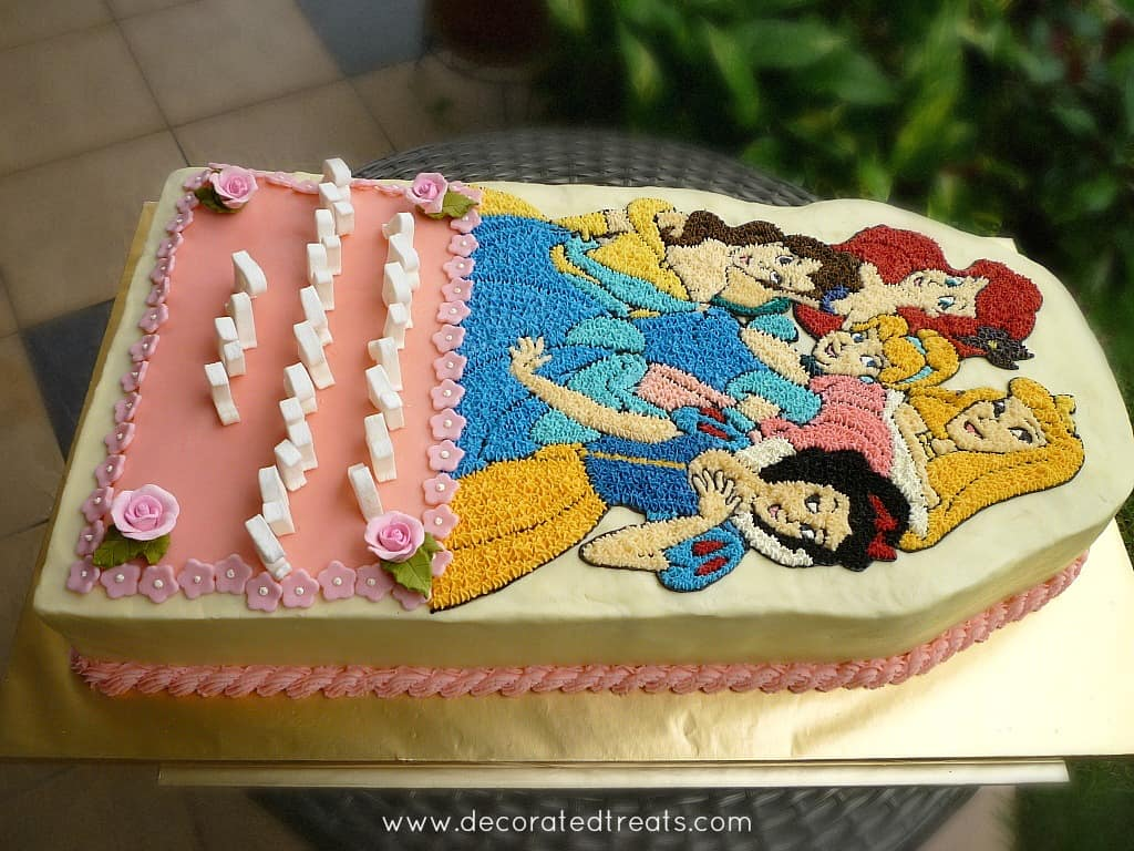 A buttercream cake decorated with images of Disney Princesses in buttercream piping