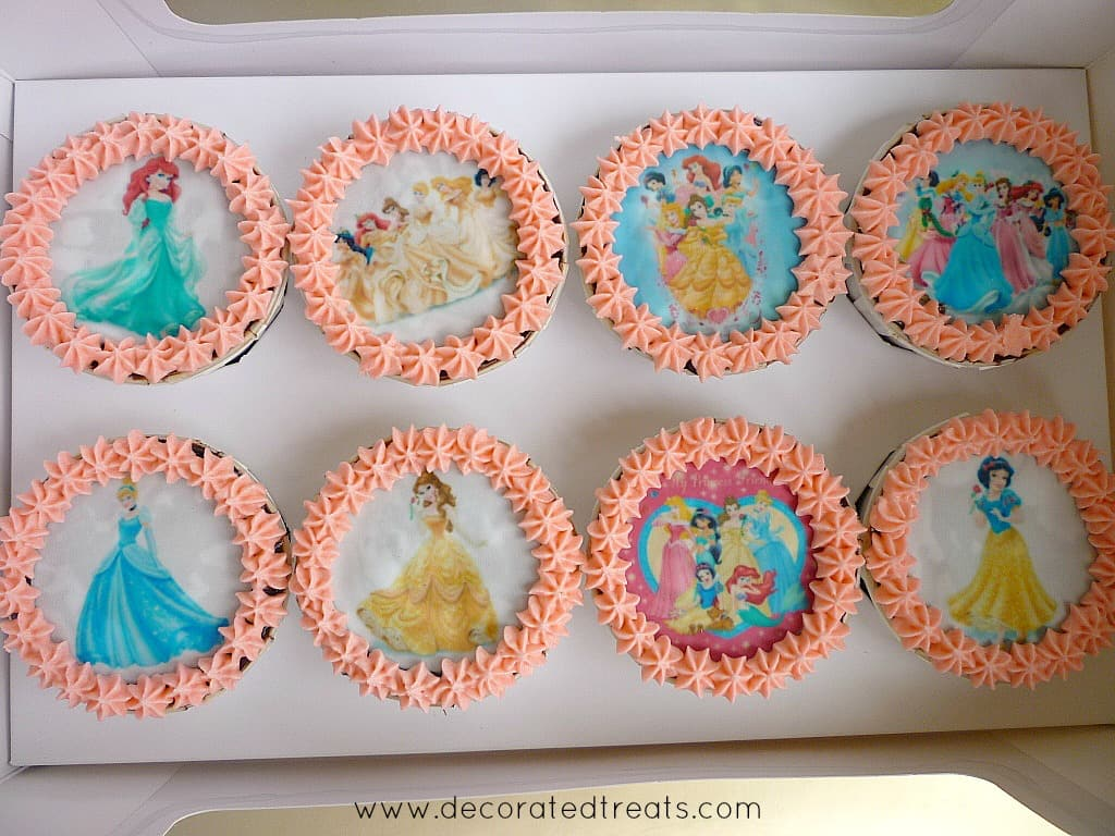A set of 8 cupcakes decorated in Disney Princesses images and pink buttercream border