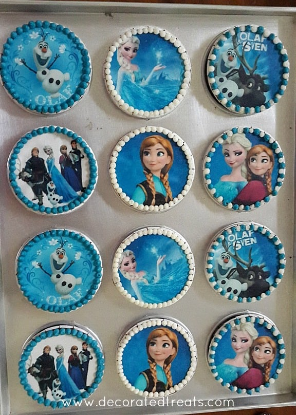 A set of 12 cupcakes decorated with edible images of characters from the movie Frozen