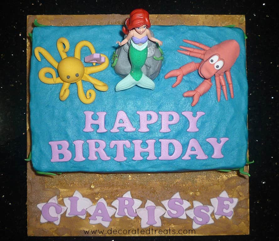 A Little Mermaid sheet cake decorated in buttercream and toy Ariel topper. On Ariel sides are fondant Sebastian and a yellow octopus