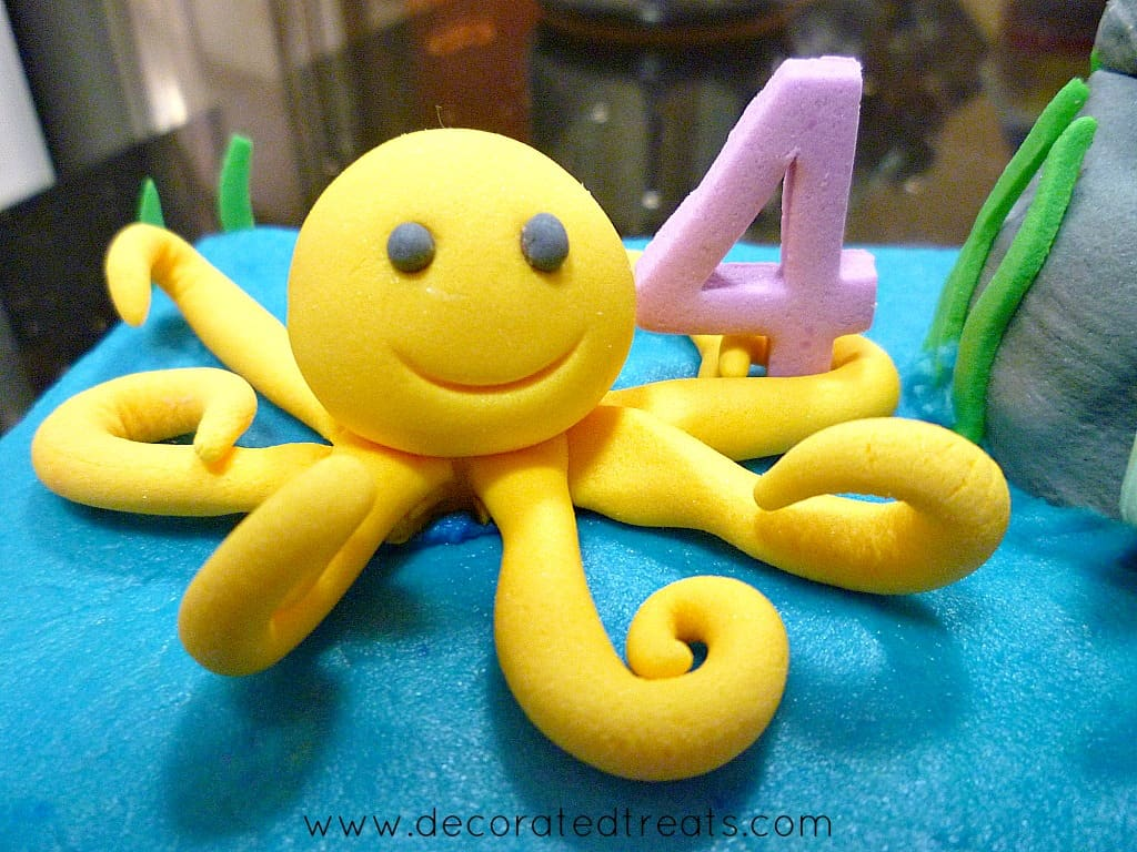 Fondant octopus in yellow, holding a number 4