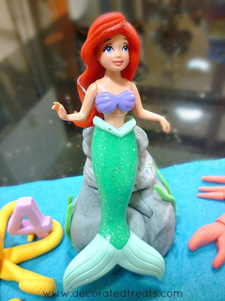 Ariel the Little Mermaid cake topper on a fondant stone on a cake