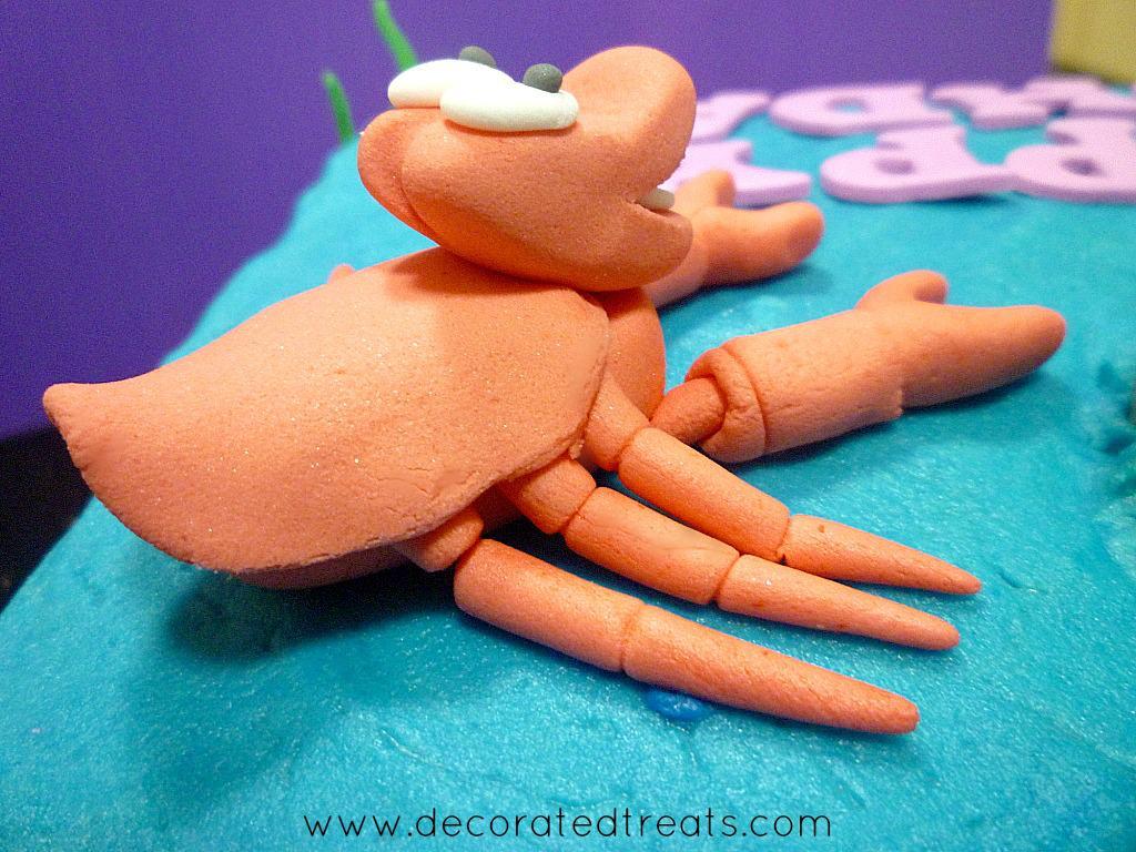 Sebastian cake topper made of fondant, on a buttercream covered cake