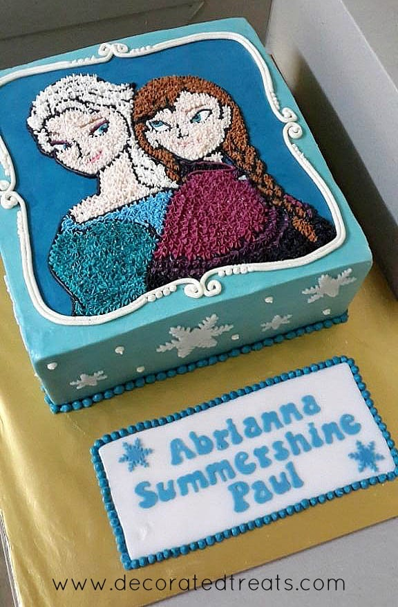 A square cake covered in blue icing with Anna and Elsa's images piped in buttercream