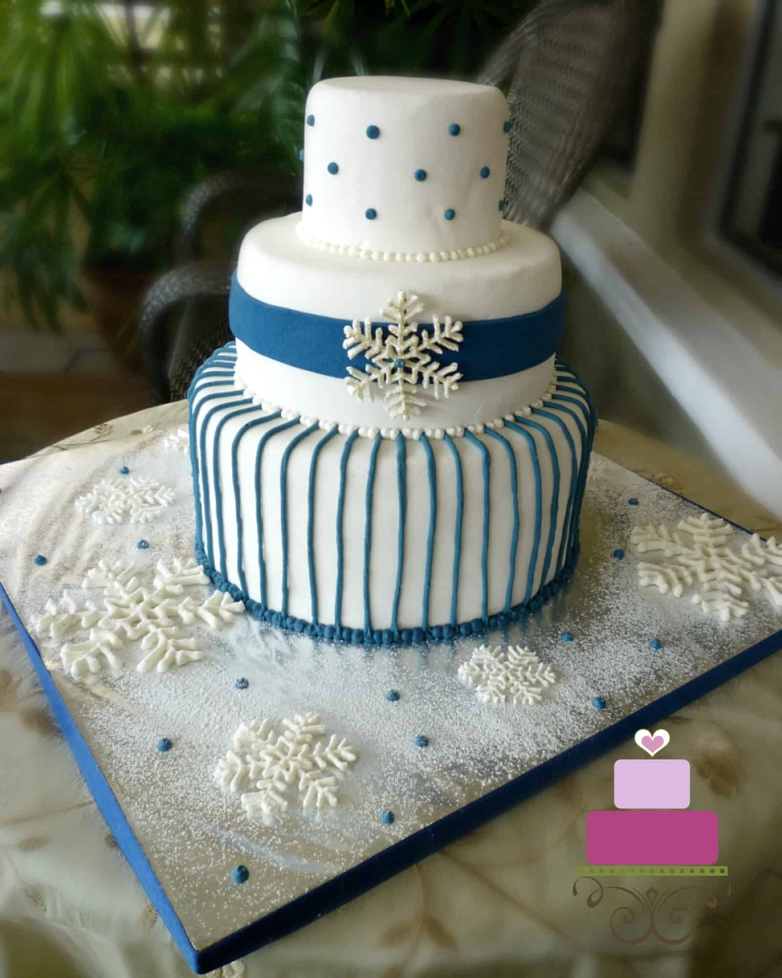 A three tier white cake decorated with blue stripes and white royal icing snowflake.