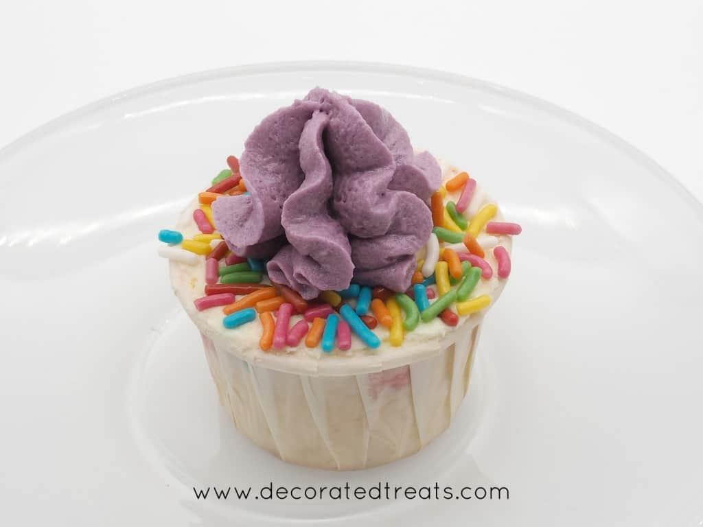 A cupcake decorated with purple buttercream swirl and colorful funfetti