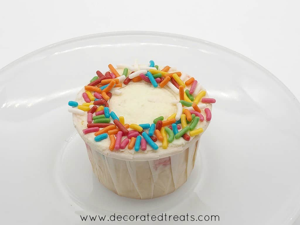 The sides of a cupcake decorated with sprinkles