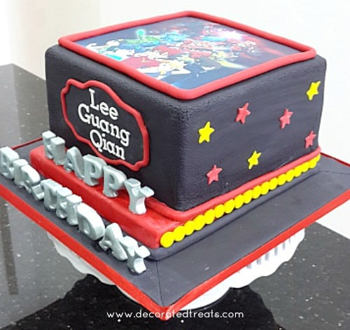 A black square cake with the Tenkai Knights edible image on top. Cake is decorated with red and yellow stars and the Happy Birthday alphabets in silver 3D