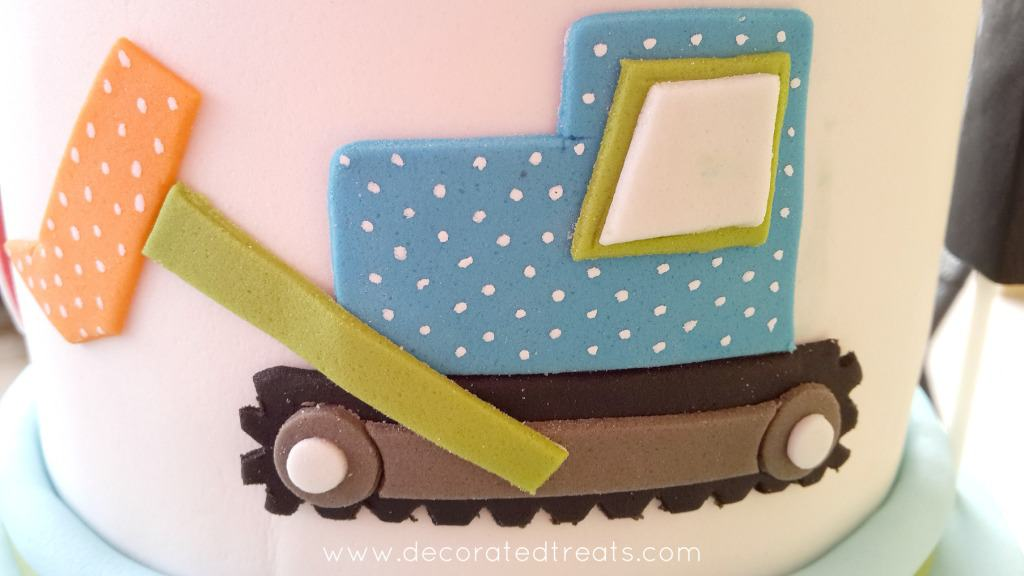 A blue 2D fondant truck on the sides of a cake