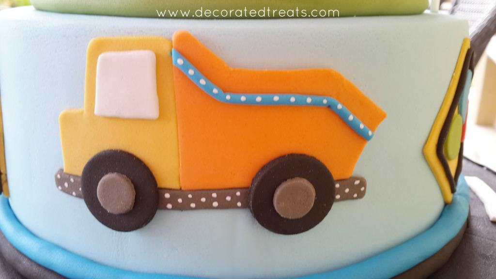 An orange truck in fondant on the side of a cake