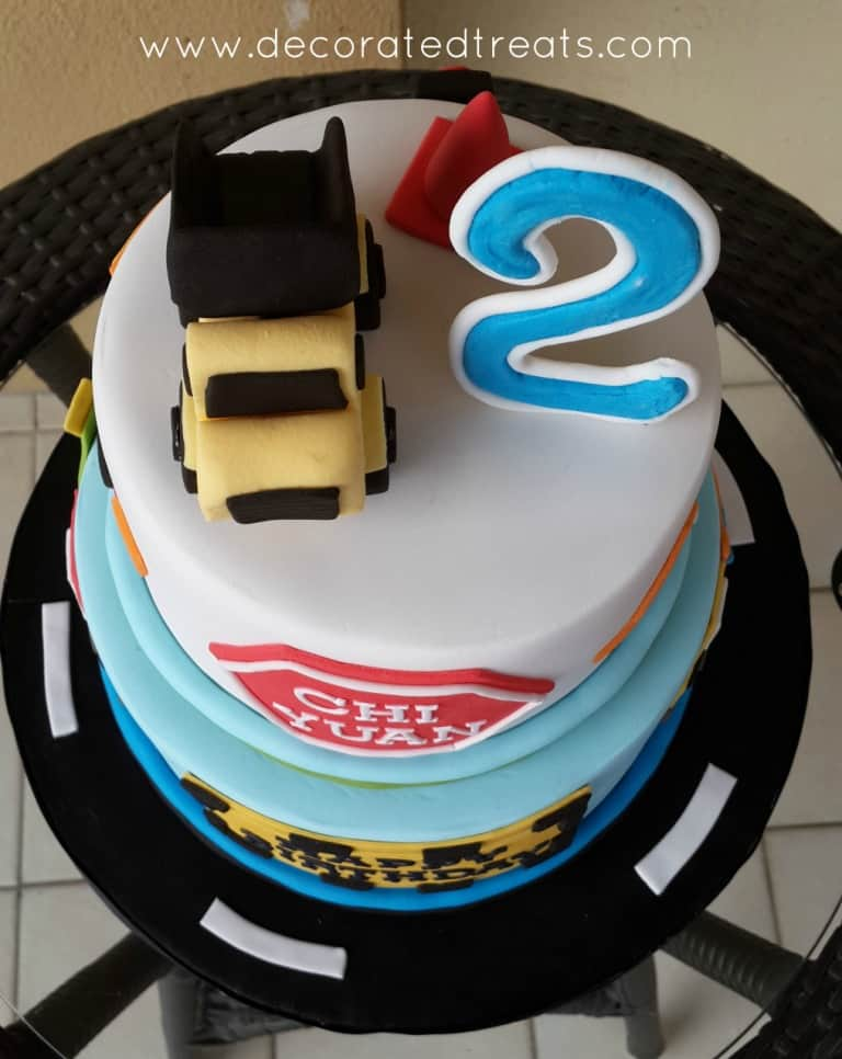 Top view of a 2 tier cake decorated with a yellow and black fondant truck topper