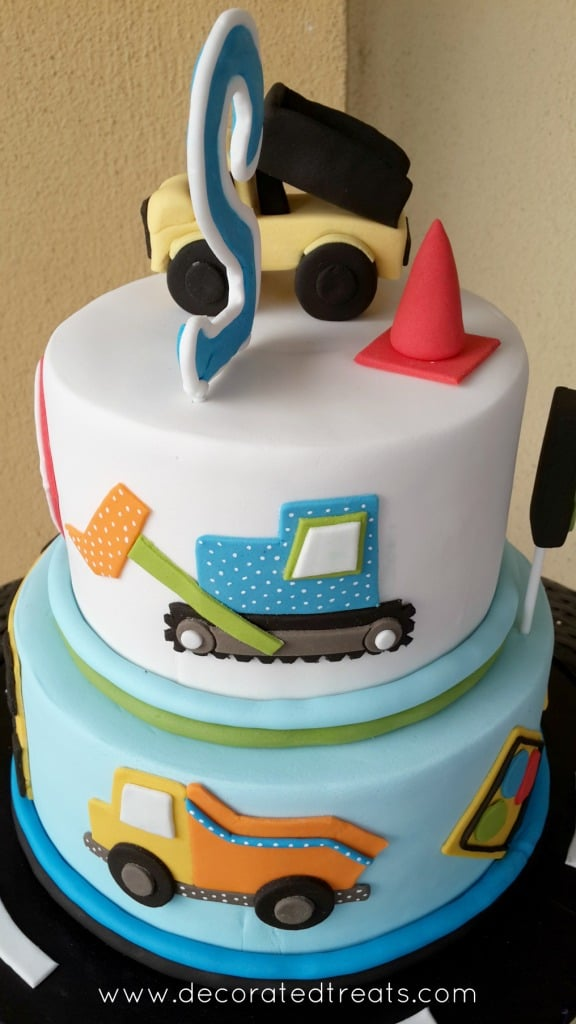 A 2 tier cake with truck topper, and the sides decorated with a blue truck.