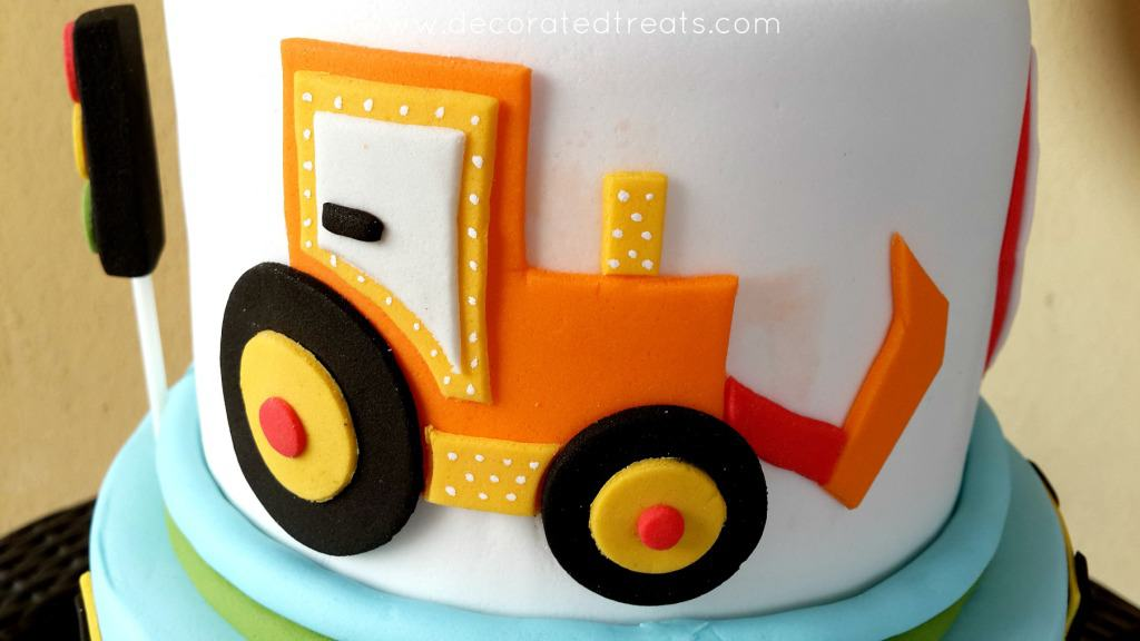 A 2D orange truck on the sides of a cake