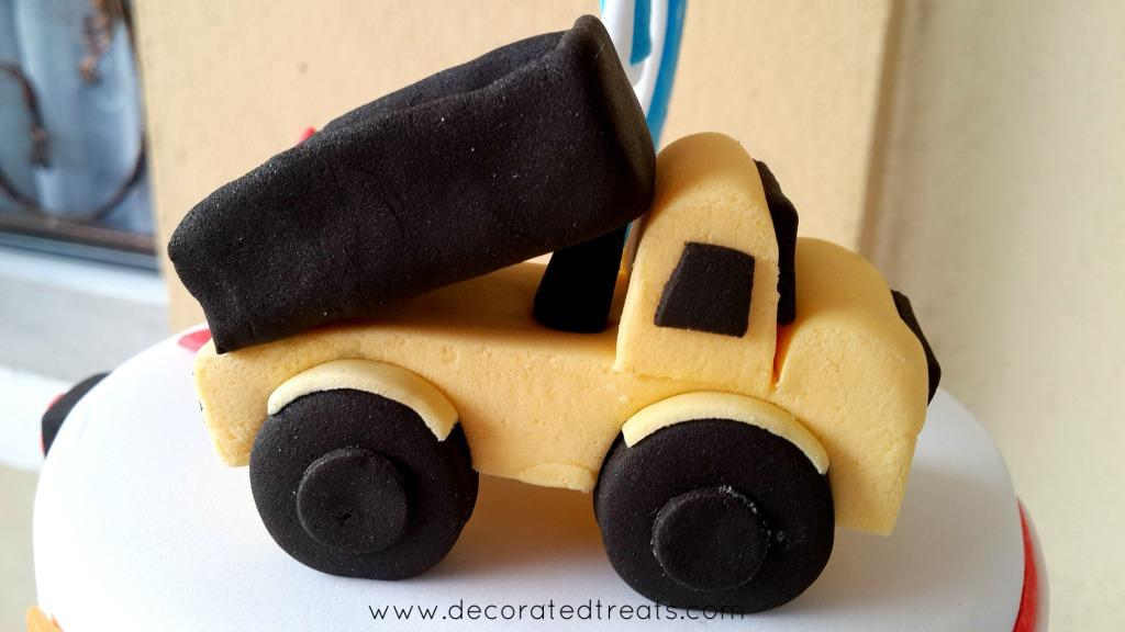A yellow and black truck topper made of fondant