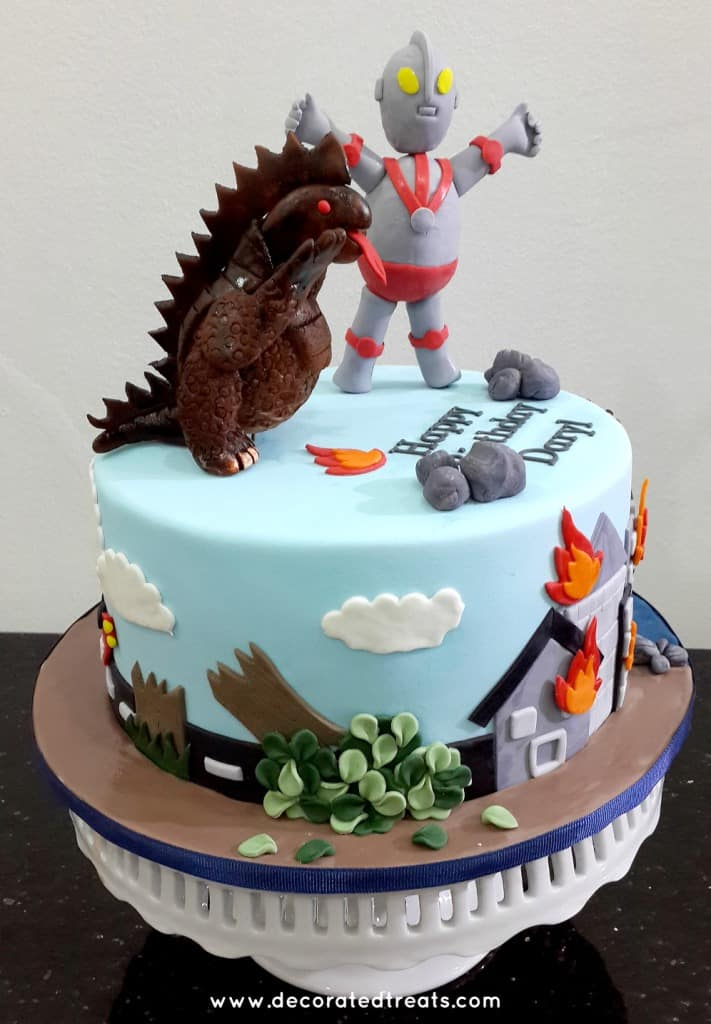 A round cake with Ultraman and monster toppers. Sides of the cake is decorated with a fallen tree and buildings on fire