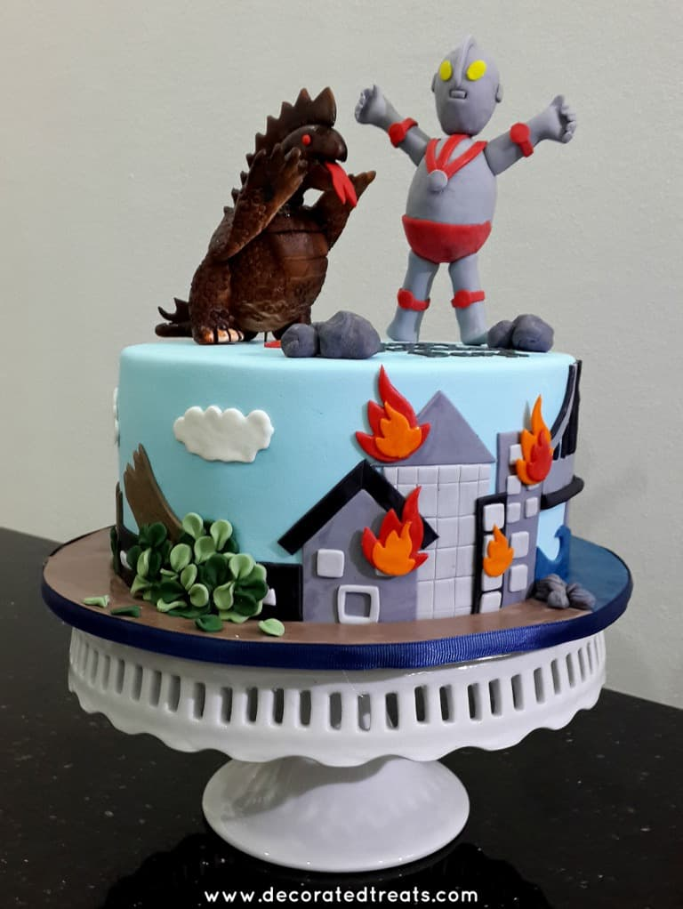A round cake with Ultraman and monster toppers. Side of the cake is decorated with buildings on fire