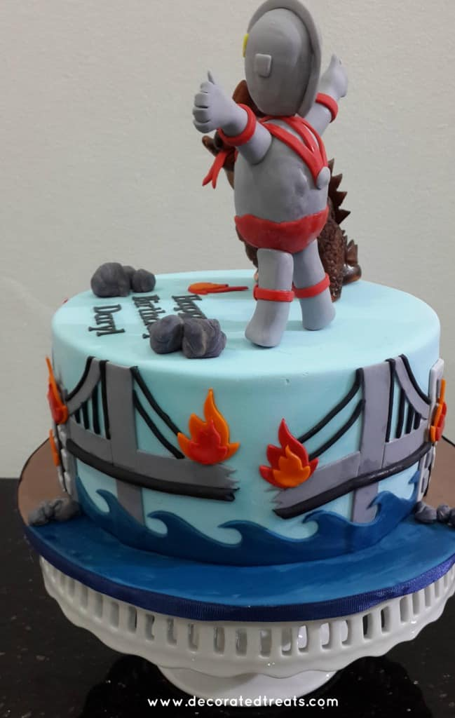 A round cake with Ultraman and monster toppers. Sides of the cake is decorated with bridge on fire