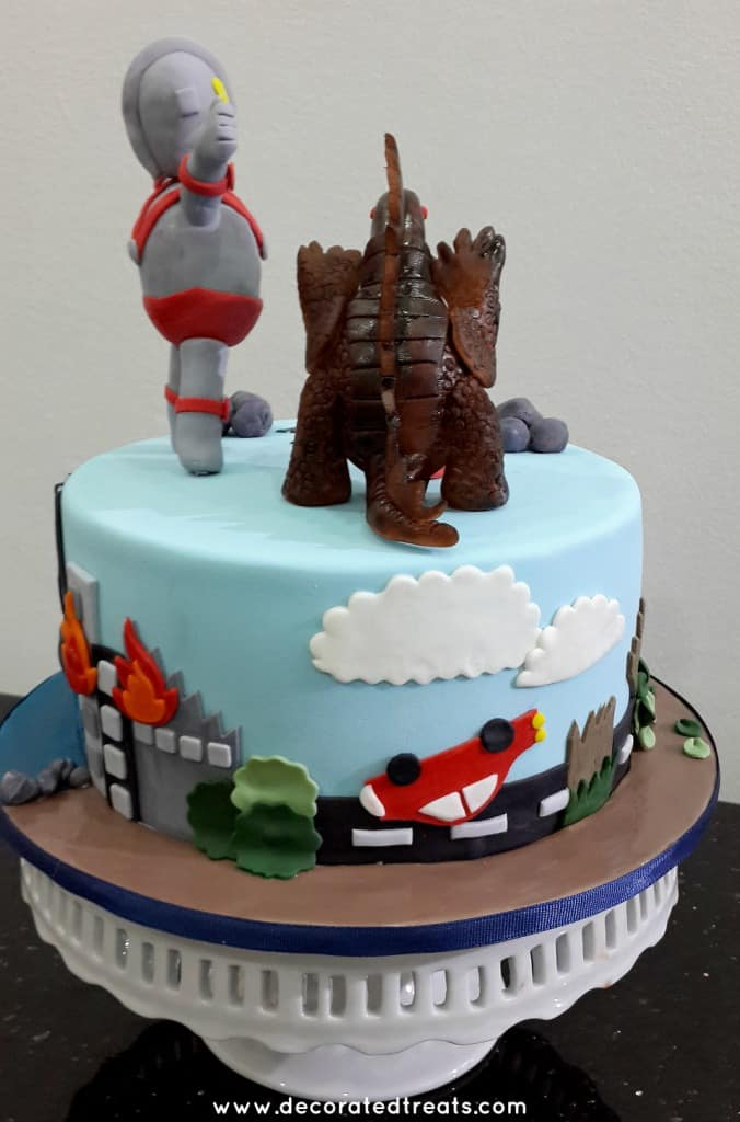 A round cake with Ultraman and monster toppers. Sides of the cake is decorated with a turtled turned car