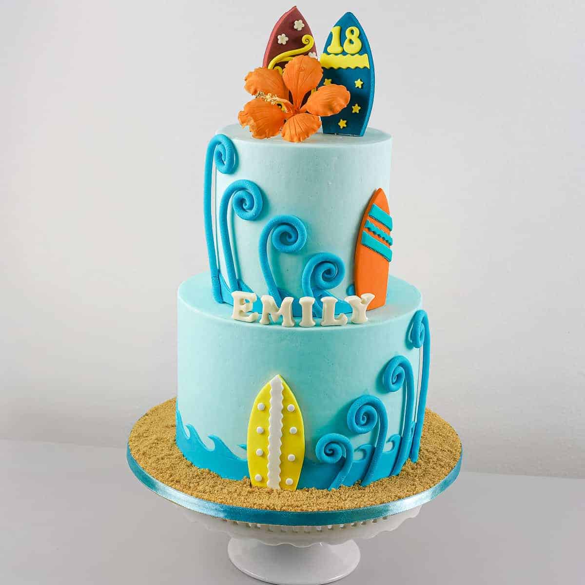 A 2 tier blue beach themed birthday cake with colorful fondant surfboards, and an orange hibiscus topper