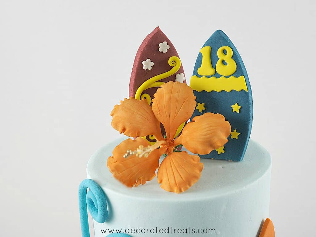 Orange gum paste hibiscus as a topper on a blue cake. In the back are 2 fondant surfboards in blue and maroon
