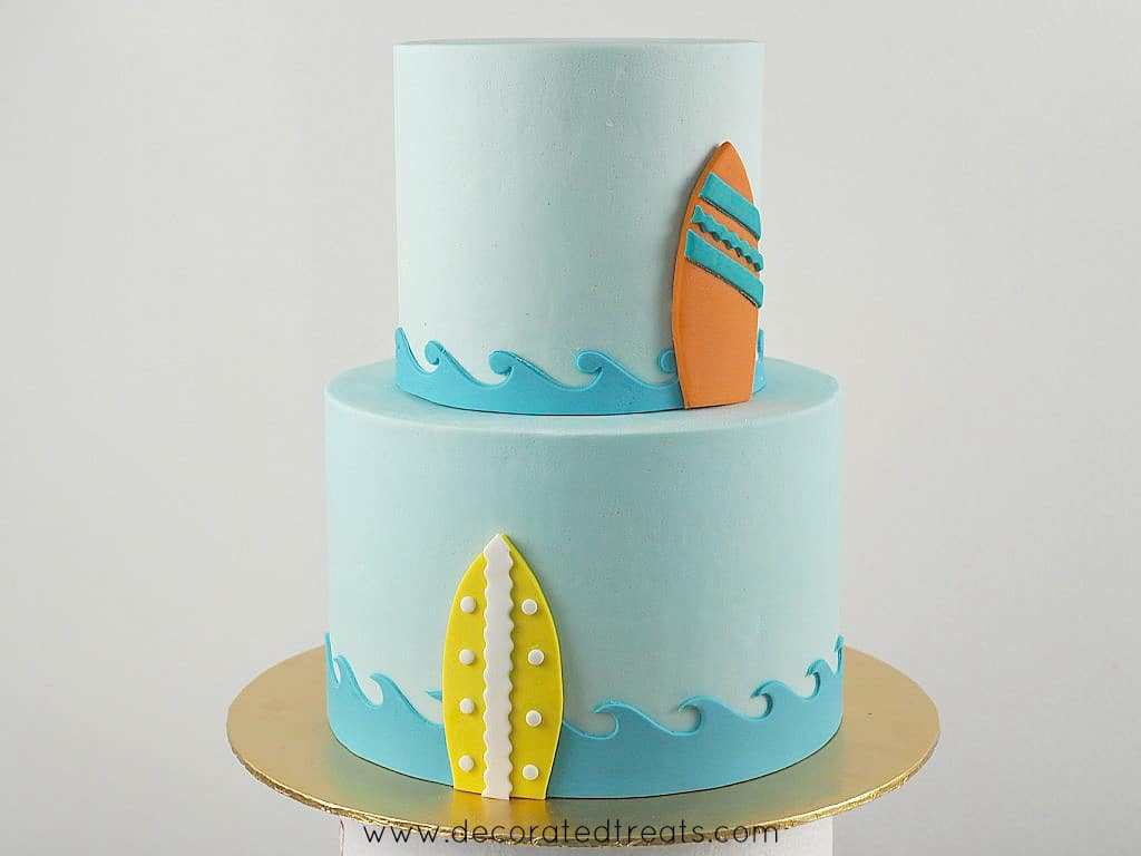 A 2 tier light blue cake with sea waves border and a yellow and an orange surfboard on the sides of each tier.