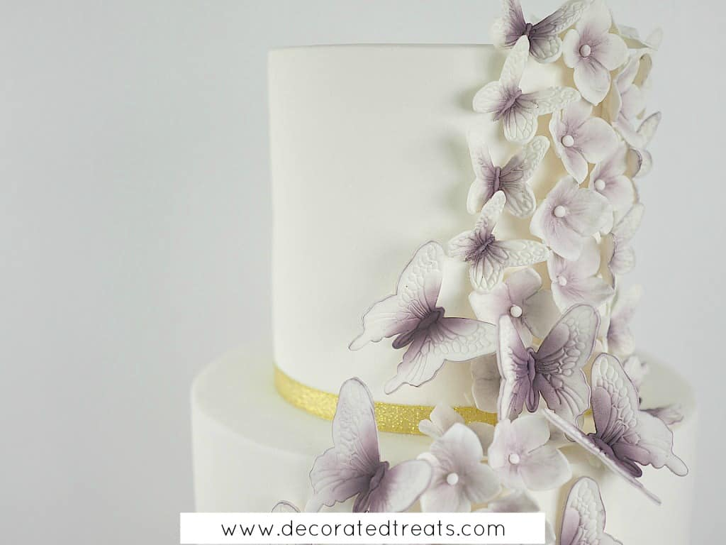 Gum paste butterflies and hydrandea in purple on a white cake with gold ribbon border