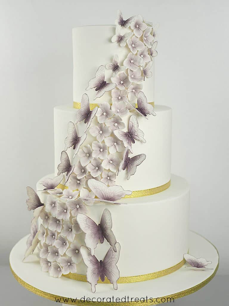 A 3 tier white wedding cake decorated with cascading gum paste hydrangea and butterflies in purple