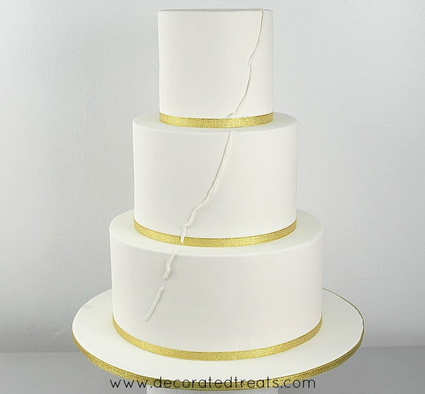 3 tier white cake with gold ribbon border