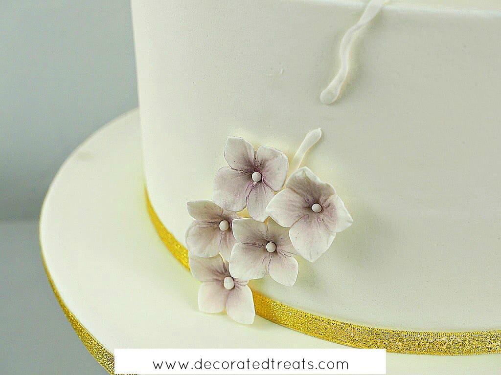 Attaching gum paste hydrangeas on a white cake