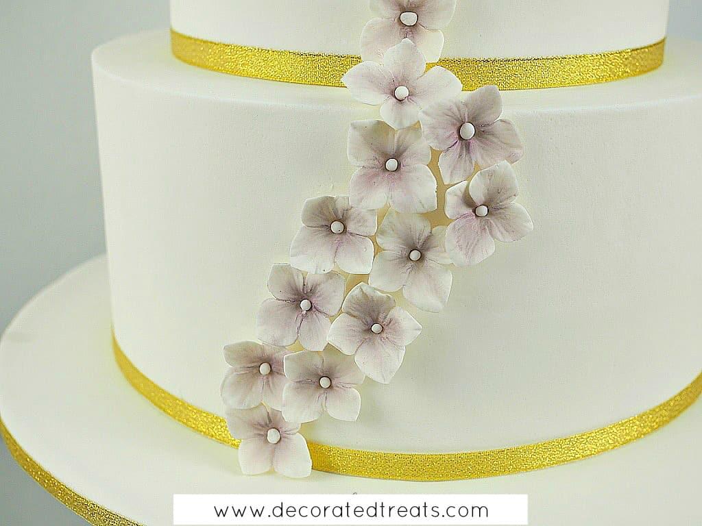 Gum paste hydrangeas in purple on a white cake