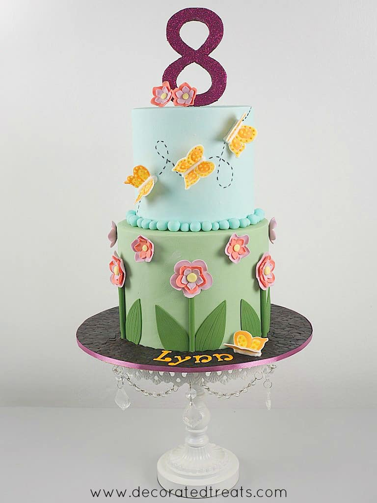 A 2 tier round cake in green and blue fondant. Bottom tier is decorated with fondant flowers and the top tier with royal icing butterflies in orange. Cake topper is a large glittery number 8