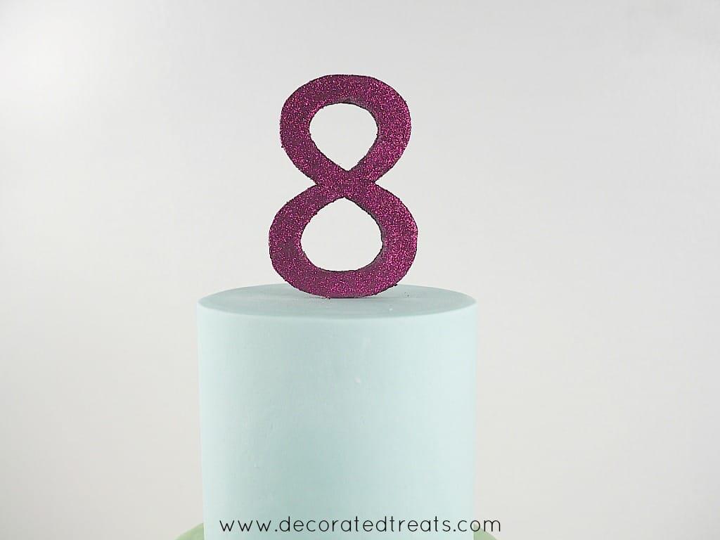 A number 8 cake topper in purple glitter