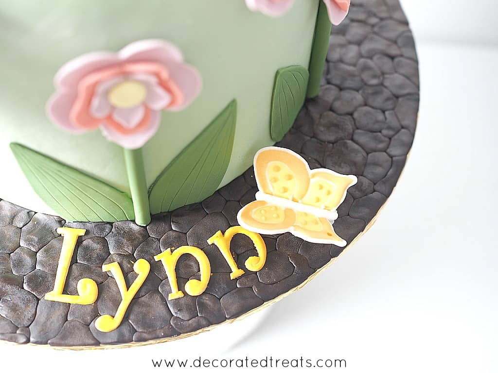 Cake board decorated in chocolate fondant and edible butterfly