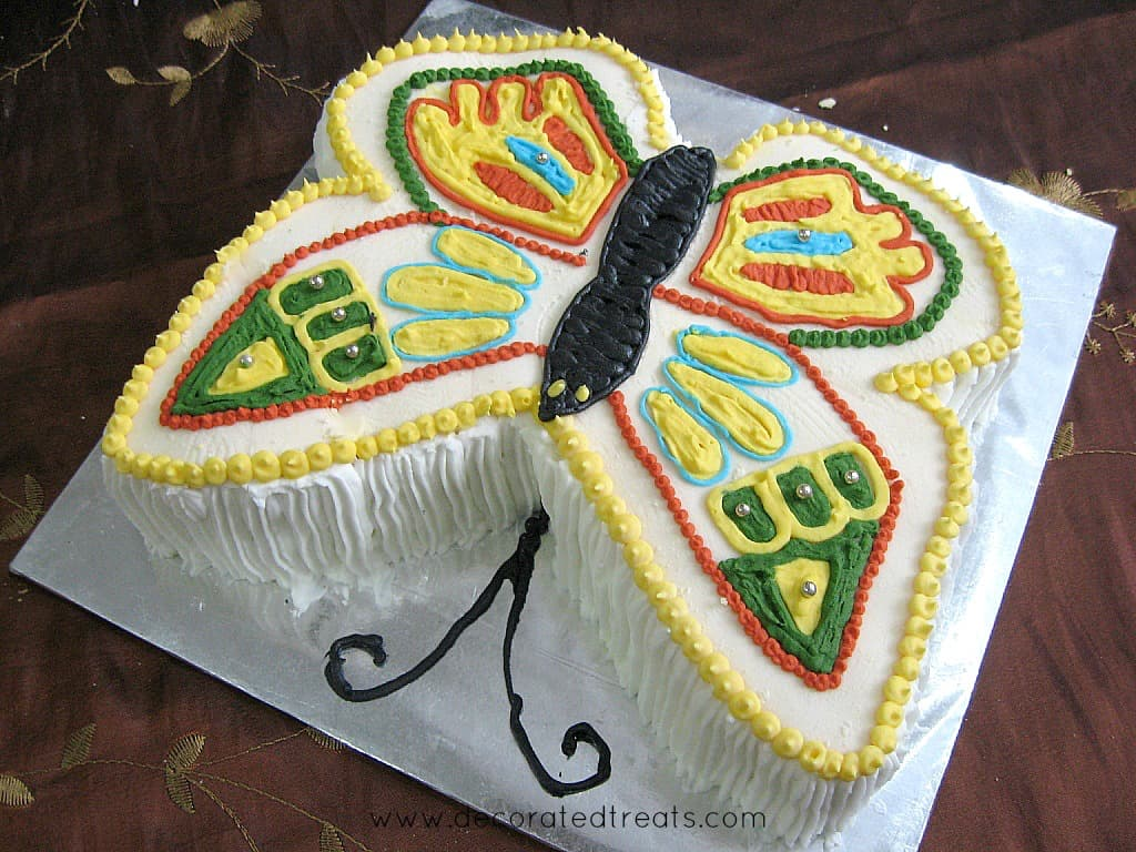A butterfly shaped cake decorated in yellow, green, red and blue