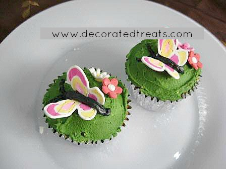 3 cupcakes covered in green icing and topped with 3d icing butterflies in pink and yellow