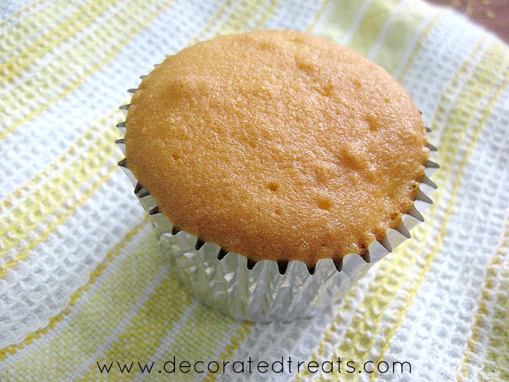 A plain cupcakes baked in silver foil, on a kitchen towel.