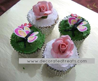 3 cupcakes covered in green icing and topped with 3d icing butterflies in pink and yellow. 2 more cupcakes are covered in white icing and topped with sugar roses