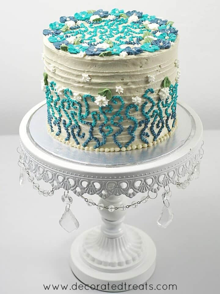 A round beige cake decorated with blue and turquoise buttercream piping and white flowers