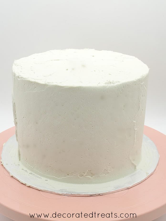 A round cake covered in plain smooth buttercream
