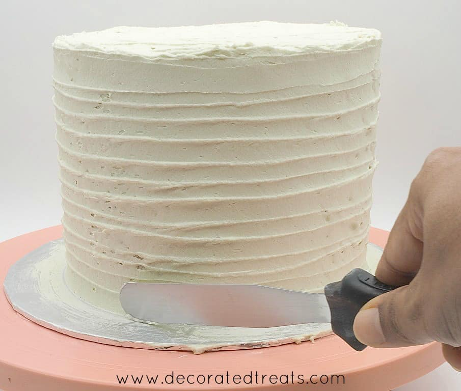 Using a palette knife to make horizontal lines on the sides of a cake