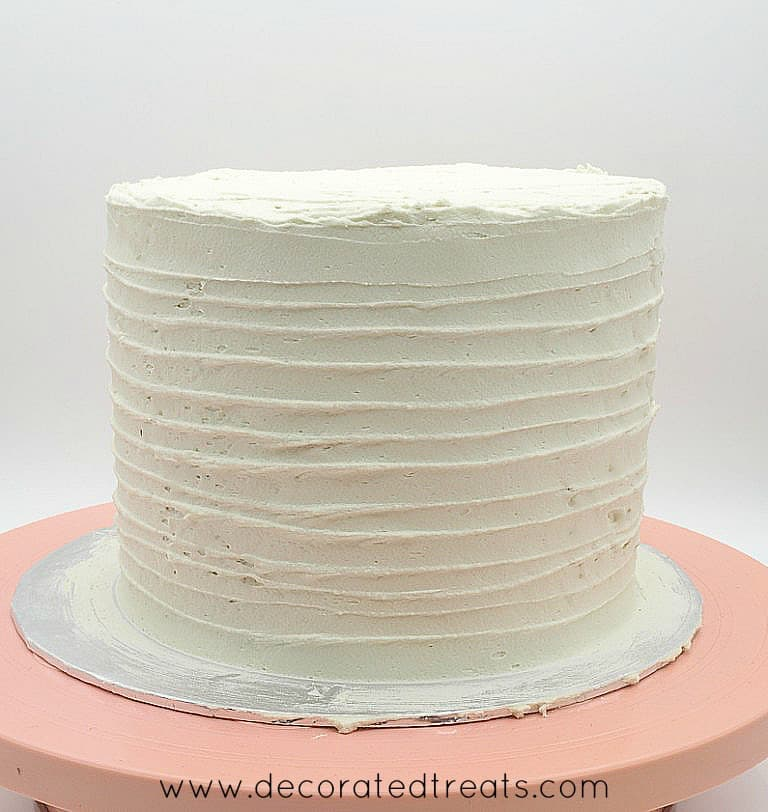 The sides of a beige buttercream covered round cake