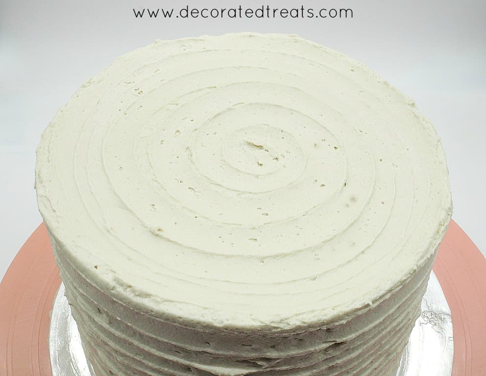 The top of a beige buttercream covered round cake