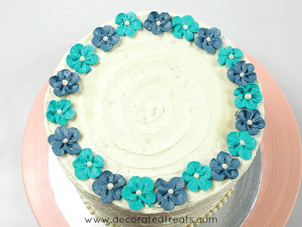 Top of a round cake decorated with blue and turquoise buttercream flowers