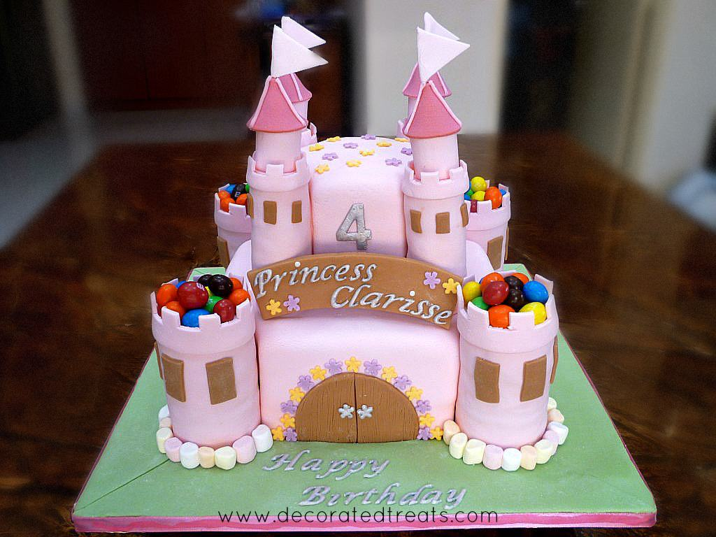 A two tier pink castle cake decorated with M&Ms and marshmallows