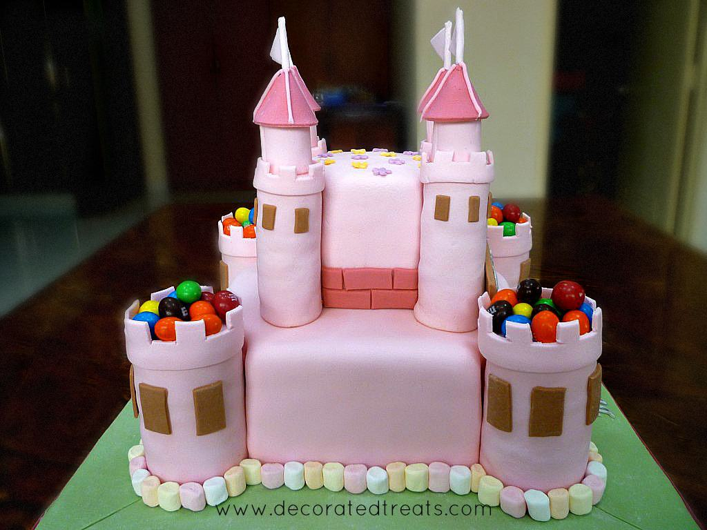 The back of a 2 tier pink castle cake decorated with M&Ms and marshmallows